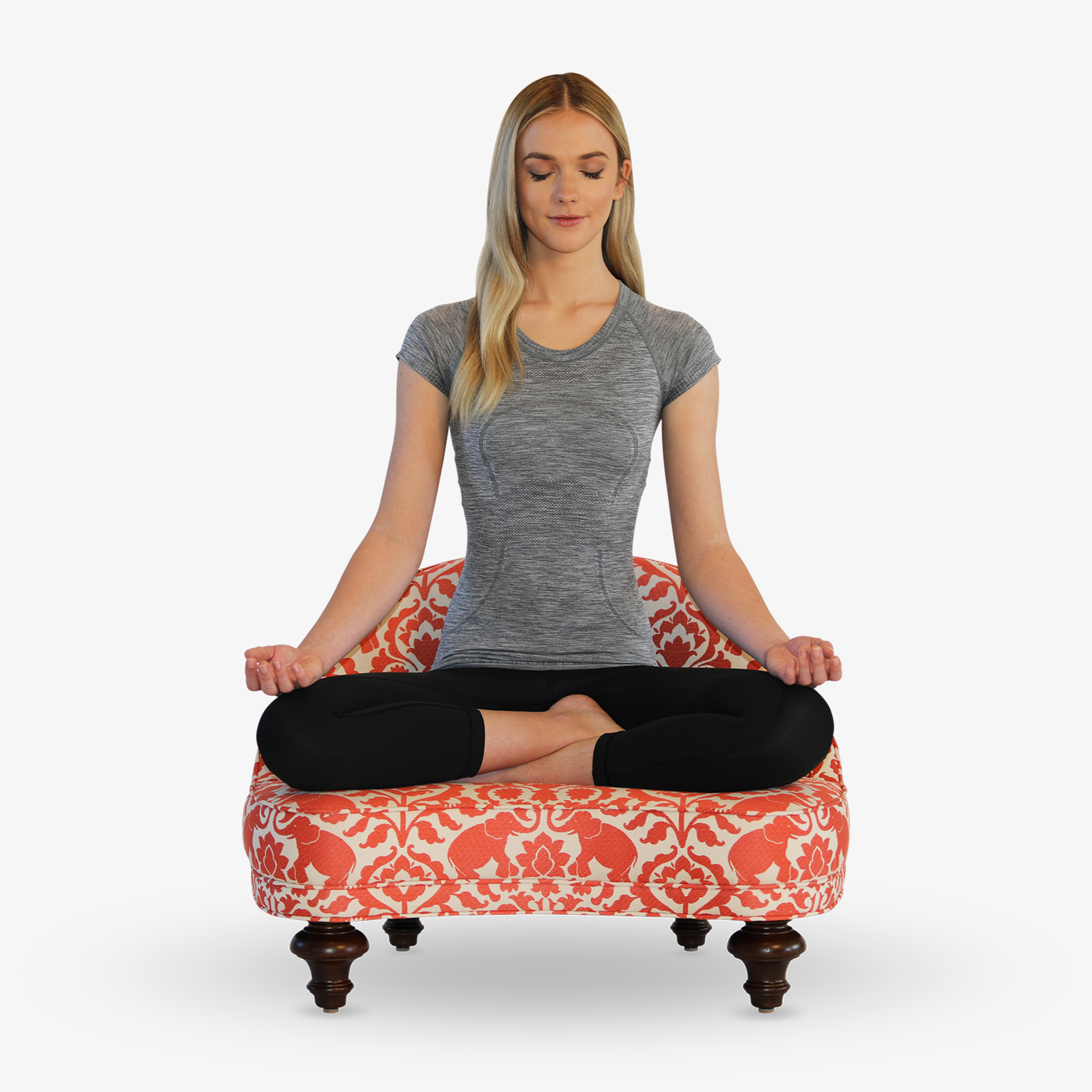 A woman meditating in the full lotus pose while using The Anahata Meditation Chair.