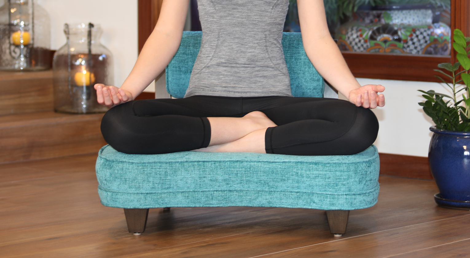 A woman meditating in Lotus Position on The Rama Meditation Chair from Zen By Design