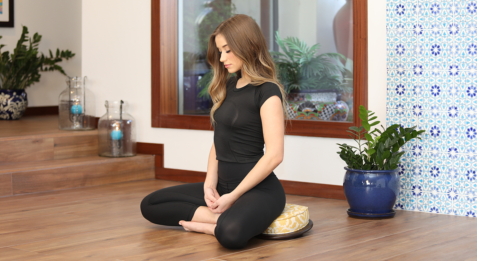 A woman meditating in The Zenfu Zafu from Zen By Design